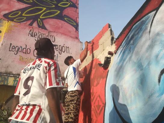 Jóvenes pintan en el sector escogido.
