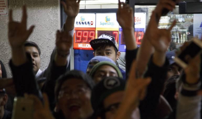 Una multitud celebra en las puertas del establecimiento donde se vendió una de las tres apuestas ganadoras del sorteo de lotería con el mayor premio de la historia de Estados Unidos.