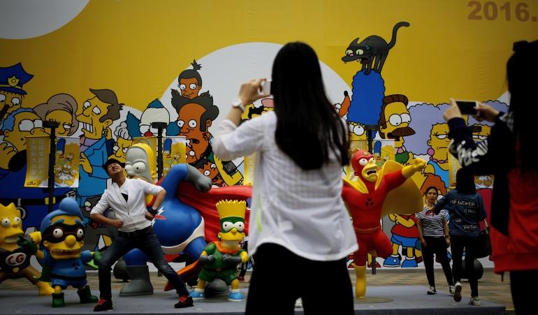 """Un hombre posa para una foto con estatuas de personajes de la serie de dibujos animados """"Los Simpson"""" en en un centro comercial en Pekín"""