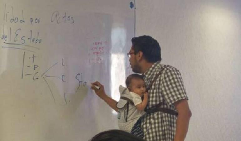 Profesor que cargó el bebé de su alumna: Profesor carga el bebé de una alumna para que ella tome apuntes de la clase