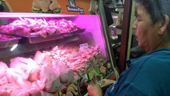 La señora se debate entre si comprar o no pollo. O simplemente comprar patas de pollo para una sopa. Porque no le alcanza.