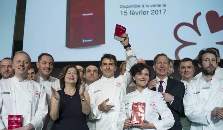 El chef francés Yannick Alleno (c) muestra la edición francesa de la Guía Michelín 2017.