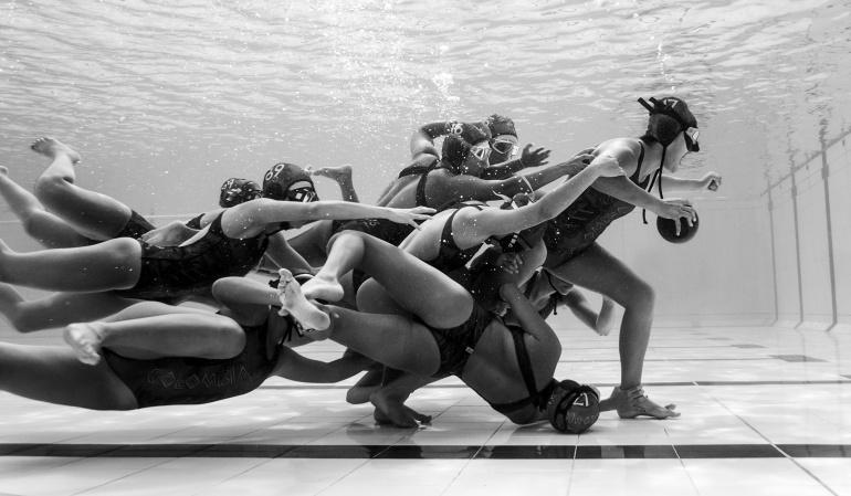 La fotografía retrata el momento en el que un equipo de rugby femenino subacuático se encuentra en el instante decisivo de un encuentro.