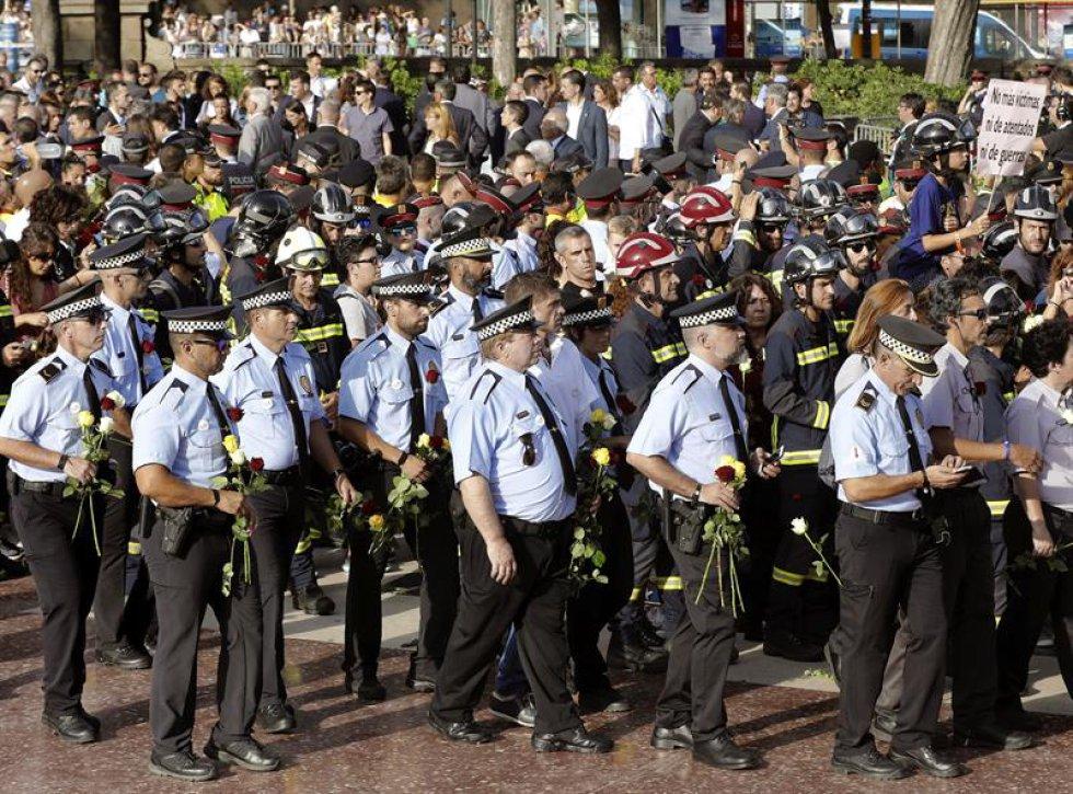 Miembros de la Guardia Urbana y los Bomberos de Barcelona portan rosas durante la manifestación.