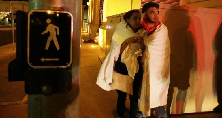 Varias personas permanecen a la entrada del hotel Mandalay Bay, cerca del lugar donde se produjo un tiroteo indiscriminado en Las Vegas, Estados Unidos