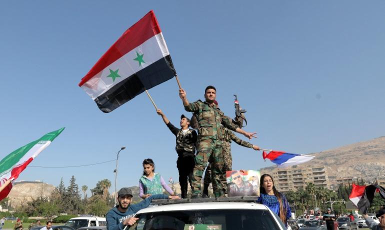 Soldados sirios ondean su bandera nacional junto con las de Irán y Rusia durante una concentración en apoyo al Gobierno sirio celebrada en la plaza de Umayyad en Damasco.