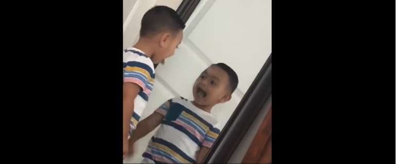 Niño se mira en el espejo y su reflejo es más rápido que él.