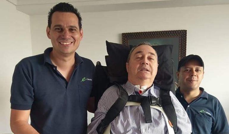 El profe Montoya se pone de pie pero con ayuda de soportes