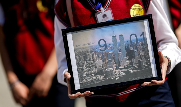 Estudiantes  sostienen fotografías de las Torres Gemelas de Nueva York durante una marcha con motivo del 17 aniversario de los atentados de 2001