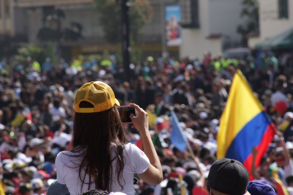 Con banderas y camisetas blancas las personas esperan al papa.