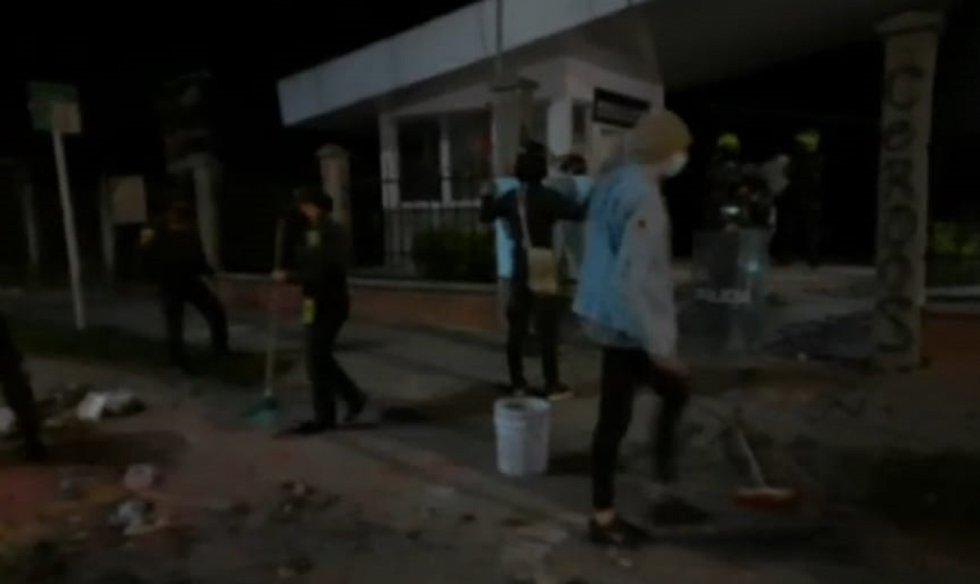 Algunos de los manifestantes y policías recogen las piedras y escombros que provocaron los daños en el CAI Fundadores de Armenia