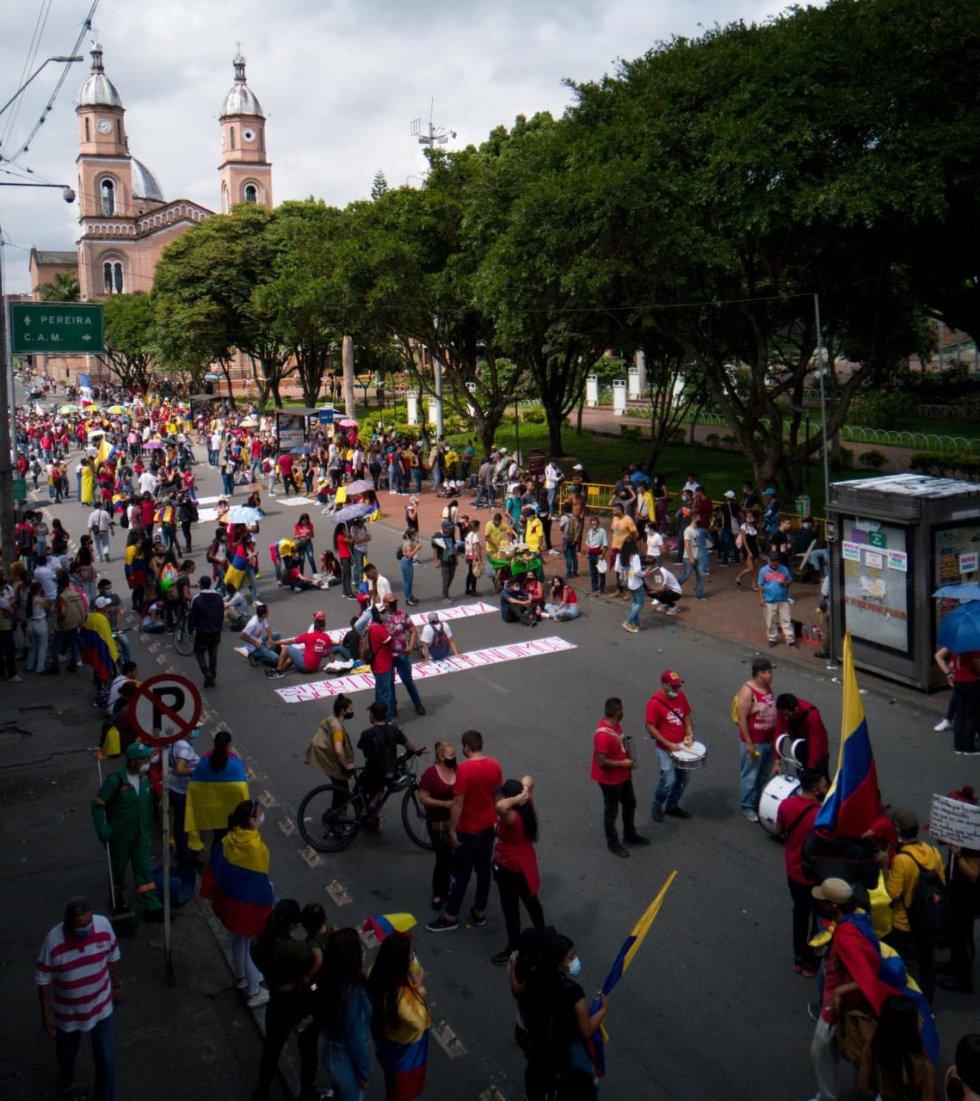 Los estudiantes con camiseta roja en plena carrera 18 en plantón en medio de la marcha