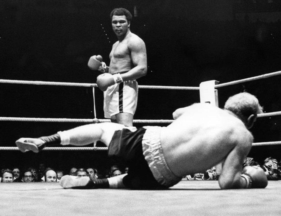 Una foto de archivo datada el 25 de mayo de 1976 de boxeador de peso estadounidense pesado Muhammad  Ali (detrás) después de llamada - hacia fuera su desafiador británico Richard Dunn (sobre tierra) en la quinta ronda de su lucha, en Munich, Alemania. Nacido como la Arcilla de Casio, embalando la leyenda Muhammad Ali, doblado como ' el Mayor, ' muerto el 03 de junio de 2016 en Fénix, Arizona, EE.UU., a la edad de 74 años, un portavoz de familia dijo. (Fénix, Alemania, Estados Unidos).