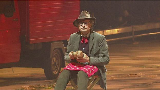 Varias camionetas de leche desfilaron durante el evento. Y en medio de todo esto, un actor se sentó, con mirada desconcertada, mientras comía un sándwich.