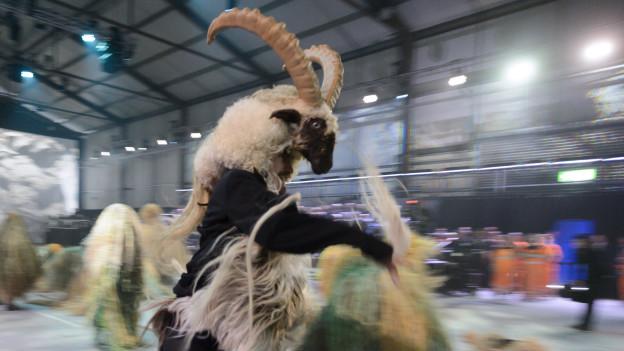 """Los """"humanos-cabras"""" se movían en el escenario, lleno de color, para el asombro de parte de los asistentes, que tomaban fotos estupefactos con sus celulares."""