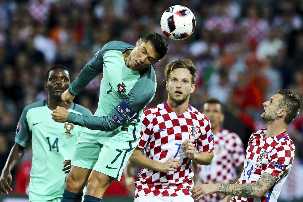 Cristiano Ronaldo y Rakitic disputan un balón elevado.