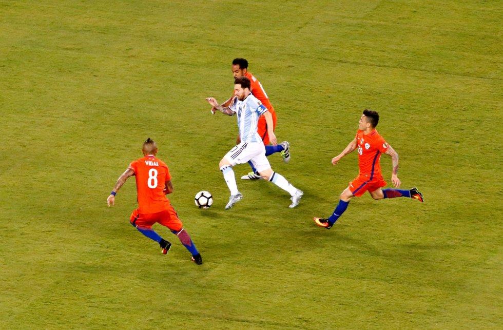Messi driblando ante la defensa chilena.