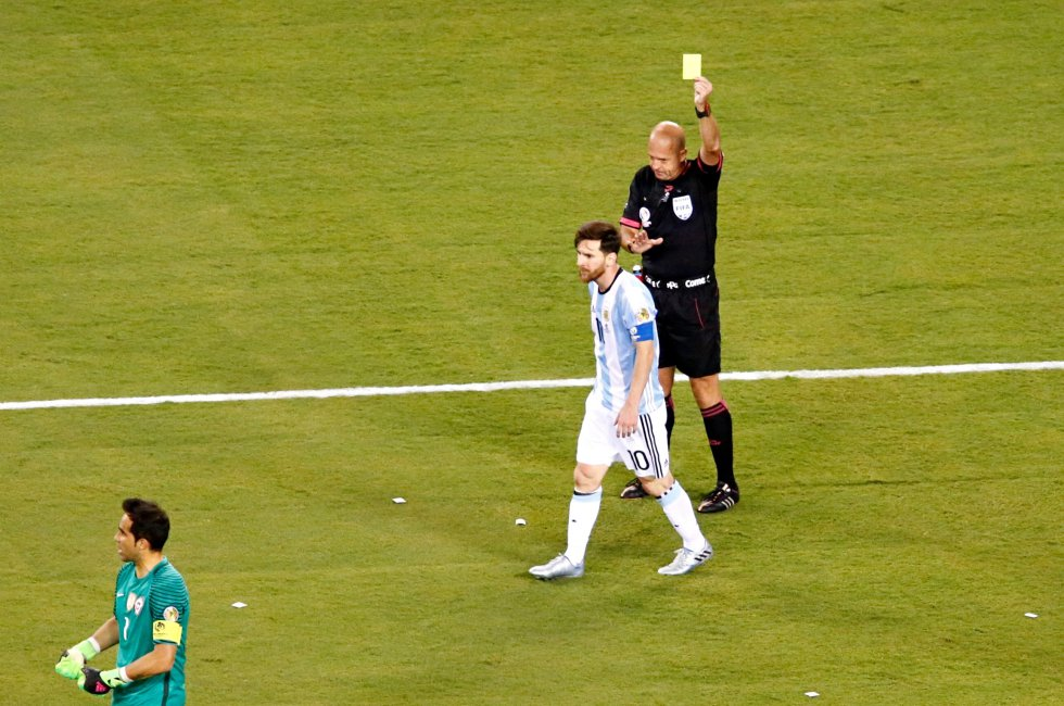 El árbitro Heber López (d) saca tarjeta amarilla a Lionel Messi.