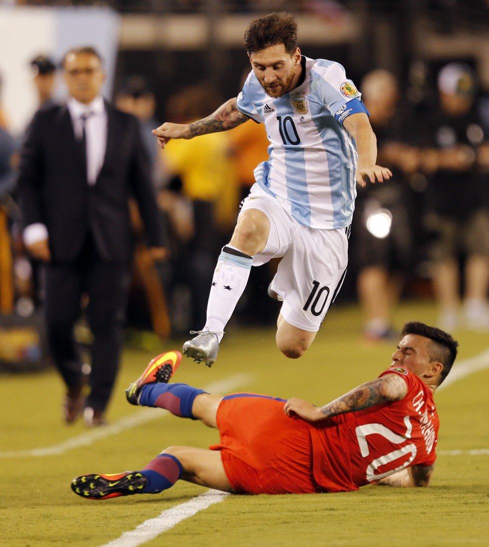 Lionel Messi (arriba) salta sobre Charles Aránguiz (abajo) de Chile.