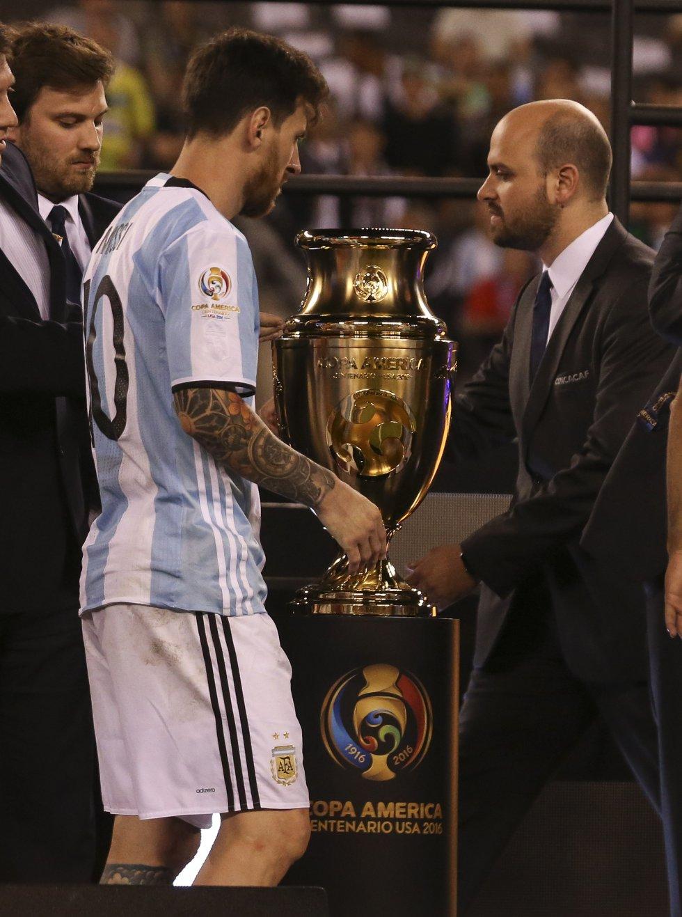 Lionel Messi (i) de Argentina pasa frente al trofeo de la Copa América Centenario luego de perder ante Chile.