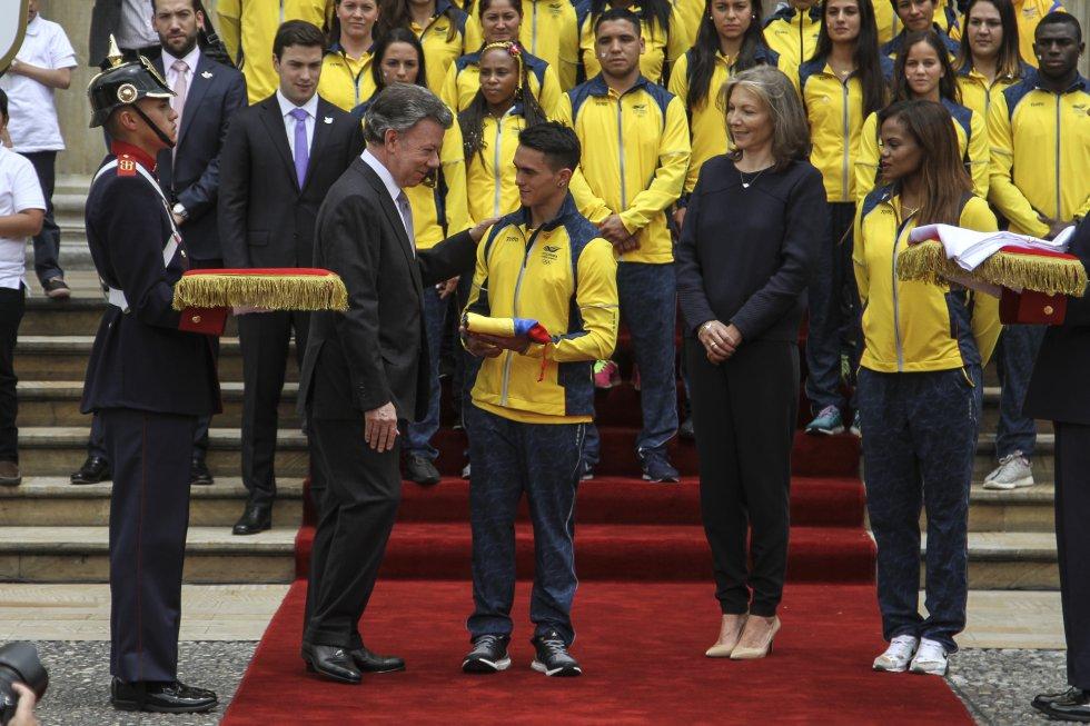 Jossimar Calvo recibe por parte del presidente la bandera de Colombia, para que se portada en la inauguración del os Juegos Olímpicos.