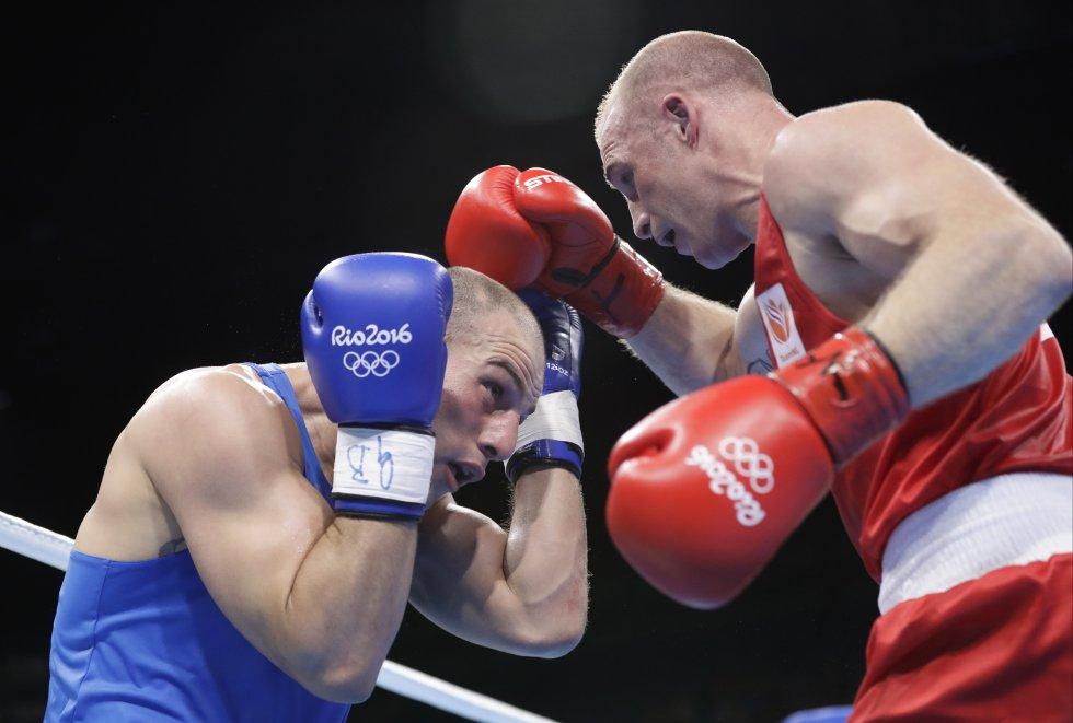 El holandés Peter Mullenberg (derecha) compite con el iraní Ehsan Rouzbahani durante la pelea de boxeo preliminar en la categoría peso pesado de 81 kg masculino.
