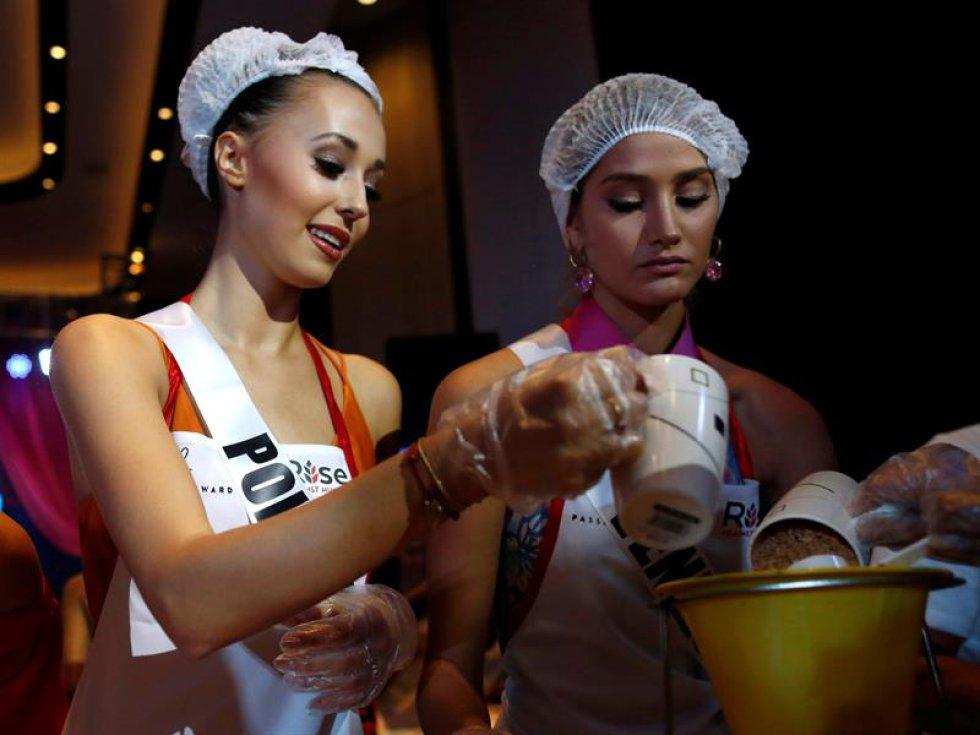 Las aspirantes a Miss Universo posan para los fotógrafos mientras colaboran en el empaquetado de alimentos
