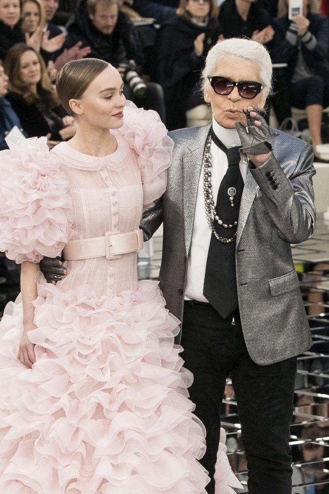 El diseñador alemán Karl Lagerfeld sale a la pasarela, acompañado por la modelo francoestadounidense Lily-Rose Depp, tras presentar su colección de alta costura primavera-verano 2017 para Chanel durante la Semana de la Moda de París.