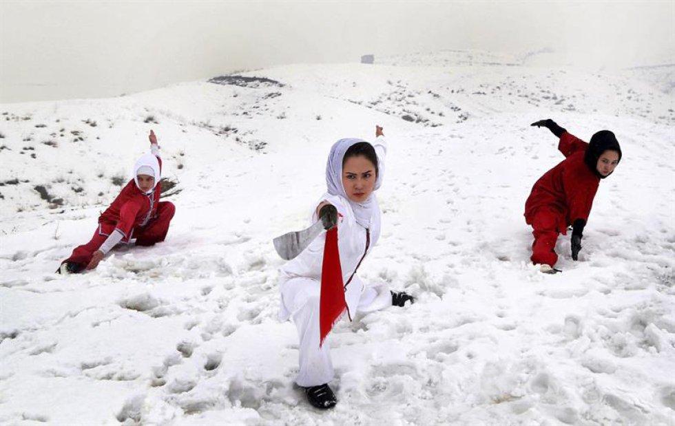 Jóvenes afganas del club de artes marciales Shaolin Wushu entrenan en la cima nevada de una montaña en Kabul.