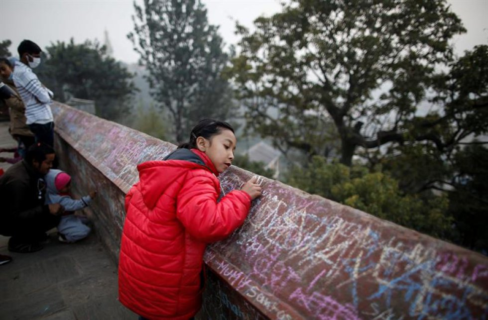 Una niña nepalí escribe en un muro un mensaje en honor a la diosa.