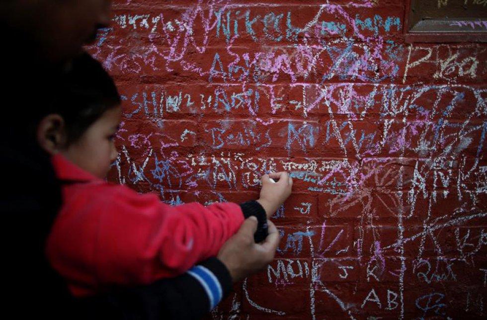Un padre nepalí ayuda a su hija a escribir en un muro un mensaje en honor a la diosa, en el Festival Shree Panchami en Kathmandu.