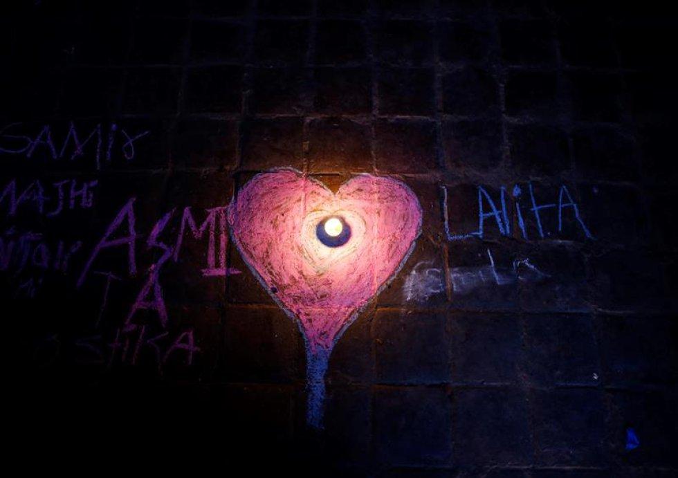 Fotografía de una vela en medio de dos nombres y mensajes en honor a la diosa.