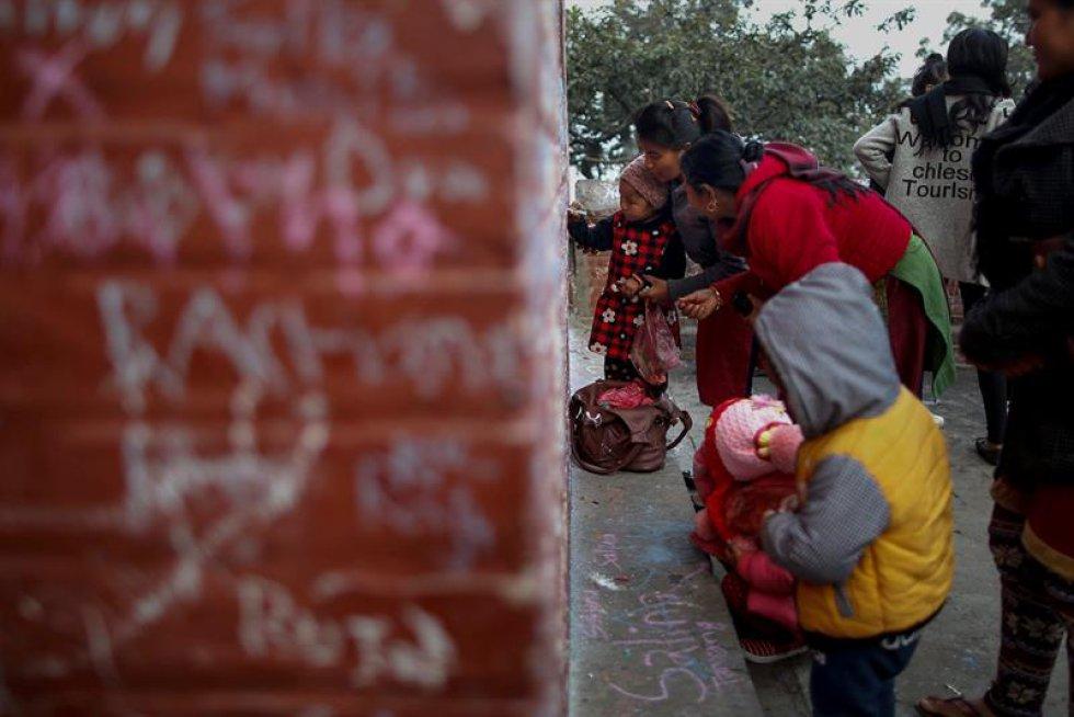 Padres nepalíes ayudan a sus hijos a escribir en un muro mensajes en honor a la diosa.