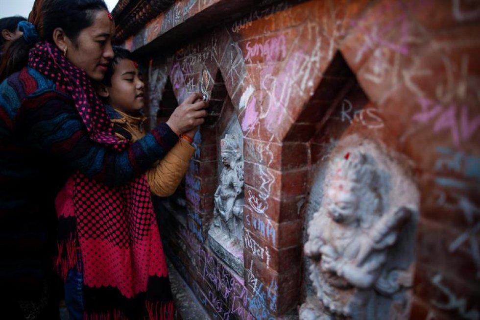 Una madre nepalí ayuda a su hija a escribir en un muro un mensaje en honor a la diosa.