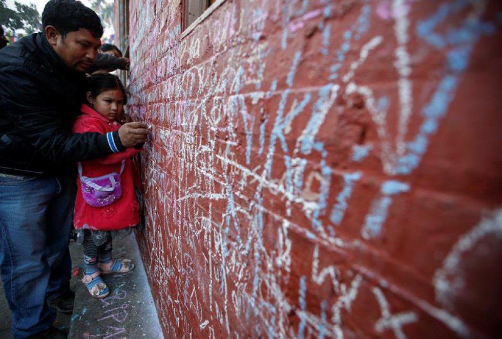 Un padre nepalí ayuda a su hija a escribir en un muro un mensaje en honor a la diosa del conocimiento, la sabiduría y el aprendizaje Saraswati