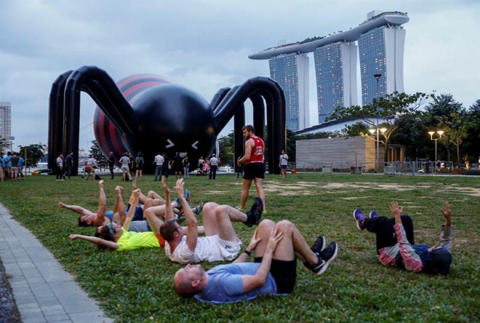 """En la instalación """"Art-Zoo"""" varias personas realizan ejercicios junto a una araña inflable."""