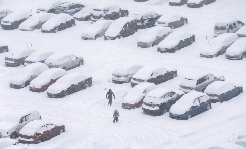 Una mujer y su hijo juegan en un parqueadero totalmente cubierto de nieve.