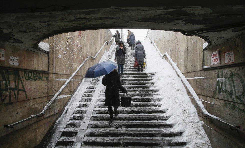 Las responsabilidades no dan espera a pesar del fuerte invierno. Una mujer baja unas escaleras cubiertas de nieve.