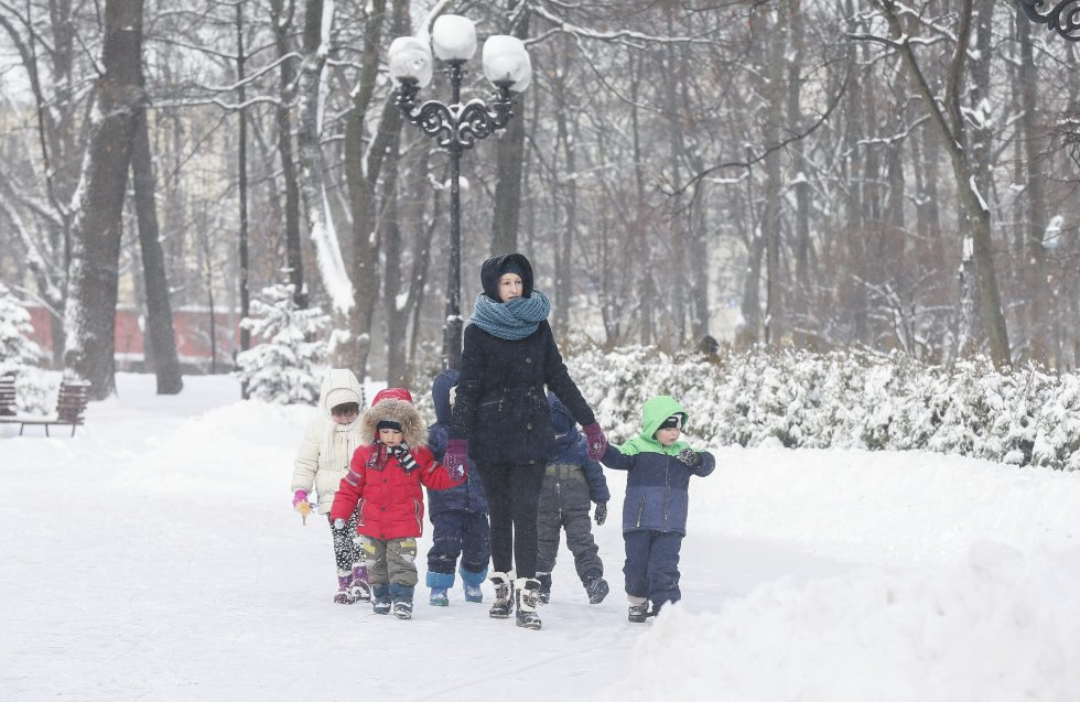Una mujer camina con varios niños por una calle cubierta de nieve en Kiev, Ucrania.