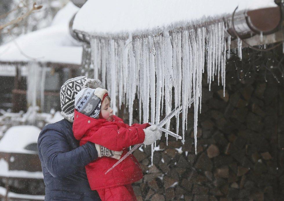 En medio del invierno, una niña juega con unas estalactitas de hielo en el centro de Kiev, Ucrania.