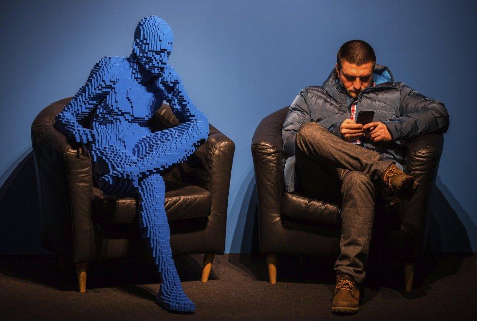 """Un visitante se sienta junto a la obra """"Hombre Azul Sentado"""" con 21.682 piezas de Lego."""