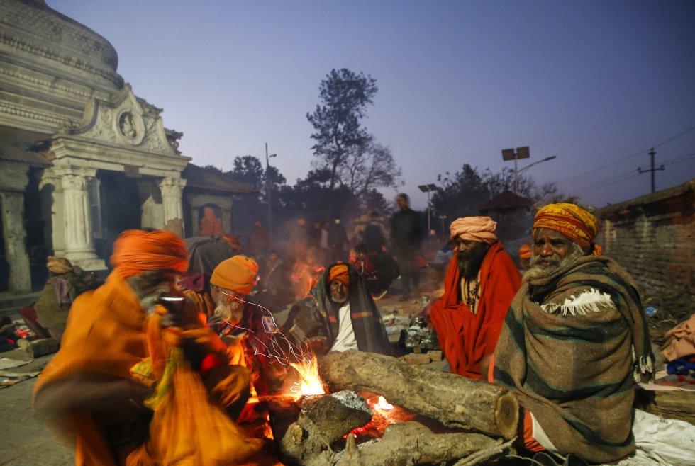 Nepal recibe cada año este festival que tiene como objetivo alabar al dios Shiva. Aquí un grupo de peregrinos hindúes se calientan ante una hoguera en el templo Pashupati en Katmandú.