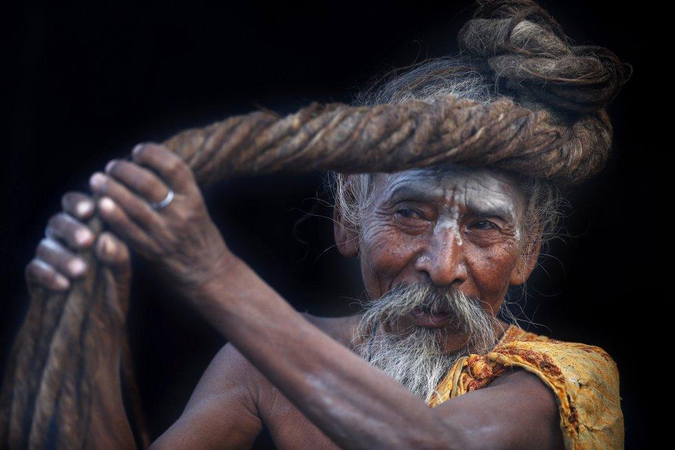 Un sadhu o asceta hindú se enrolla el pelo en la cabeza antes de ingresar al templo Pashupati como símbolo de respeto y alabanza.