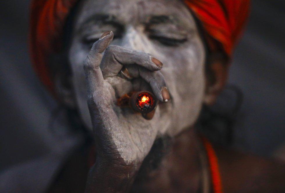 Un hombre fuma marihuana en una pipa de arcilla con el objetivo de concentrarse y alcanzar paz espiritual en el templo Pashupati.