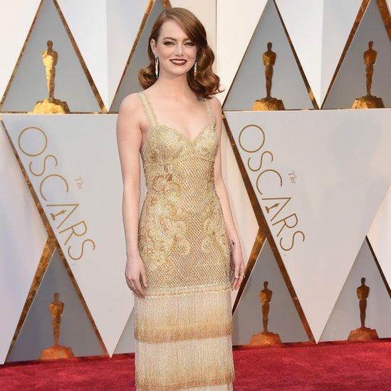 Emma Stone llevaba un vestido dorado a su llegada a la alfombra roja. La estadounidense está nominada al premio de mejor actriz por la cinta 'La La Land', la cual tiene 14 nominaciones en esta entrega.