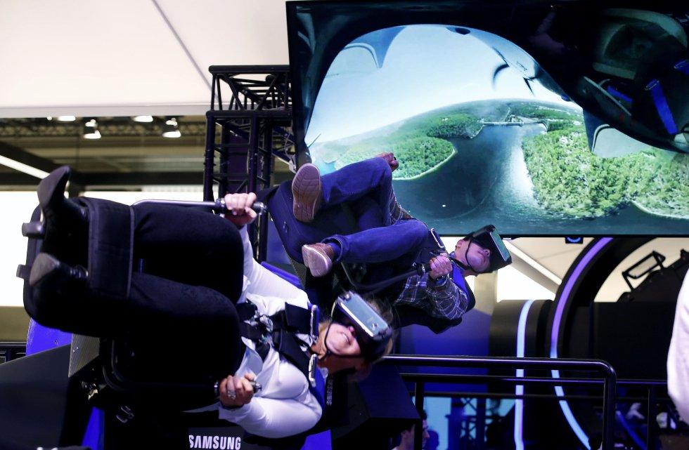 Dos visitantes prueban un simulador de vuelo acrobático de realidad virtual en el stand de la empresa coreana Samsung en el Mobile World Congress(Congreso Mundial de Móviles).
