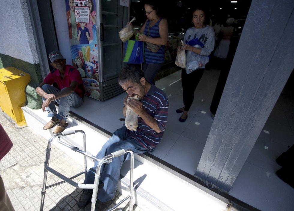 Un hombre come pan tras comprarlo en una panadería privada en Caracas, Venezuela.