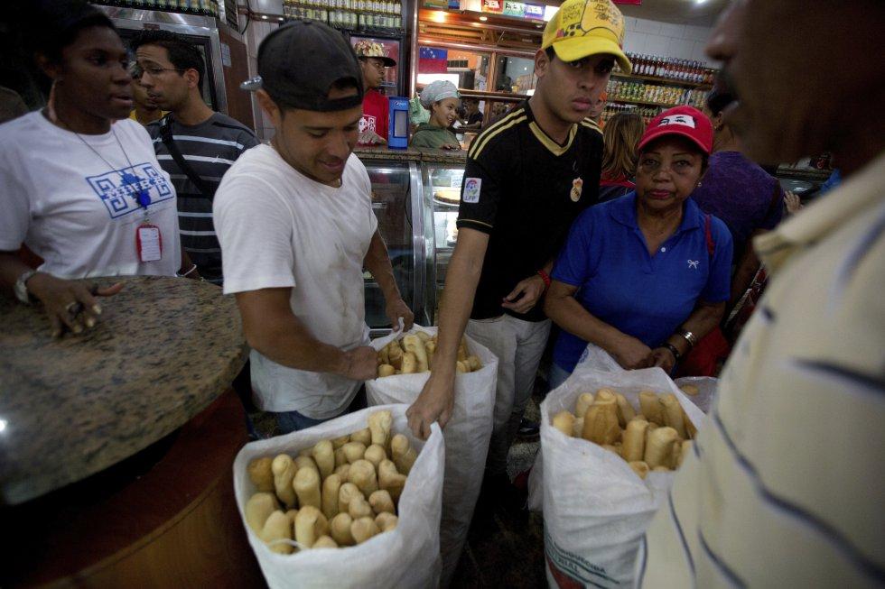 Empleados de la panadería estatal Minka trasladan barras de pan barato que será distribuido en en tiendas estatales, en Caracas, Venezuela.