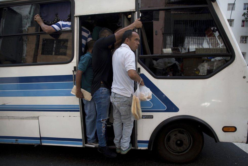 Un hombre se cuelga de la puerta de un autobús con una bolsa con pan en la mano, en el exterior de una panadería en Caracas, Venezuela.