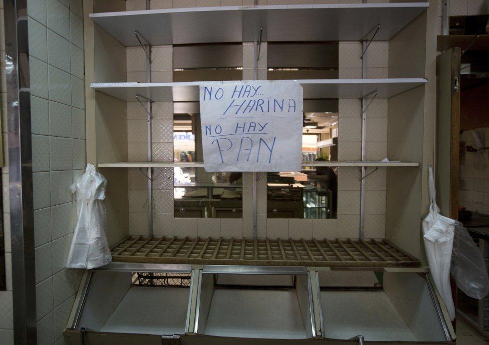 """Cartel con la frase """"No hay harina. No hay pan"""" colgado en un estante vacío en una panadería privada en Caracas, Venezuela."""